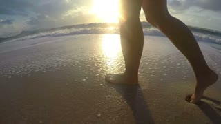 Female Legs Walking on Sand at Beach in Sunset. UHD.