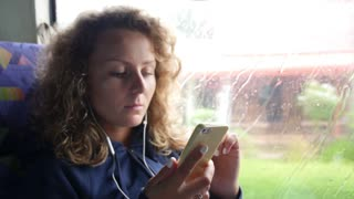 Female Passenger Listening to Music in Phone in Train or Bus
