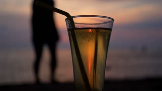 Female Silhouette and Glass of Refreshing Beverage at Sunset