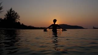 Female Silhouette Raising Arms against Sunset in the Sea. Slow Motion.