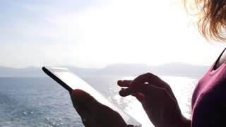 Female Traveler Using Tablet Computer in Sea on Yacht