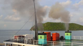 Ferry with Smoke from Engine Sailing in Sea