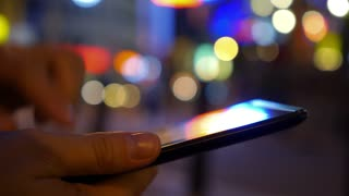 Fingers Touching Screen of Digital Tablet on Blurred Night Lights