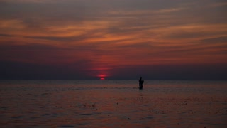 Fisherman with Fishing Net at Sunset in Sea, Thailand