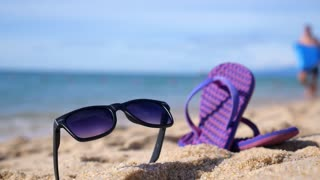 Flip-Flops and Sunglasses on Beach Against Sea