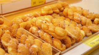 Fly on a Sweet Sugar Doughnuts in Supermarket. Insanitary Conditions in Food Store