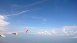 Flying Aircraft Wing through the Clouds and Blue Sky. Timelapse.