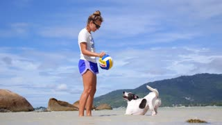 Girl Playing with Dog with Ball on Beach. Slow Motion.