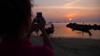 Girl Taking Photo of Sunset with Smart Phone on the Beach