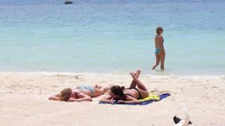Girls in Bikini Lying on Sandy Beach and Tanning in Sun with Dog.