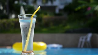 Glass of Cold Water on Pool Side in Tropical Beach Resort