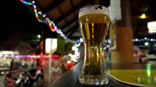 Glass of Foamy Fresh Draught Beer on Bar Counter on Night Street