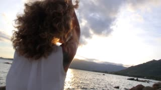 Gorgeous Curly Hair Woman Spreading Arms by Sea
