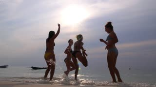 Group of Happy Young Girls Dancing at Beach in Sea