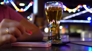 Hand Using Mobile Phone with Glass of Beer at Bar