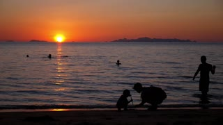 Happy Family - Mother with a Child Playing on the Beach at Sunset.