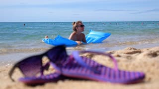 Happy Girl Swimming in Sea on Beach with Mattress