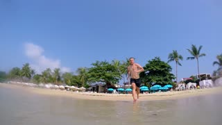 Happy Man Jump in Sea at Tropical Beach. Slow Motion.