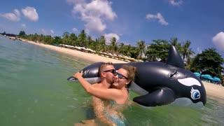 Happy Summer Honeymoon Couple Kissing in Sea