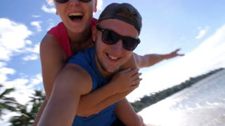 Happy Young Couple Enjoying Beach Piggyback