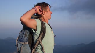 Hiker with Backpack Standing on Top of Mountain with Raised Hands