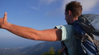 Hiker with Backpacker Standing on Top with Raised Hands