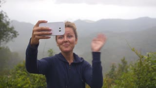 Hiker Woman Having Video Chat Using Smartphone on Top