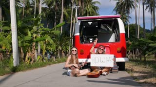 Hippy Girls Sitting on Road Making Peace and Antiwar Sign