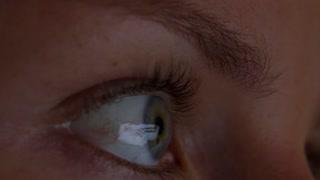 Laptop Reflection in Female Eye Working at Night. Closeup.