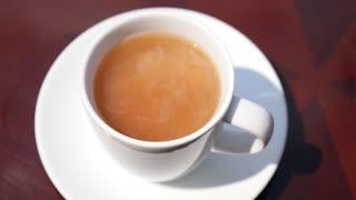 Male Hand Stir Milk in Cup of Tea