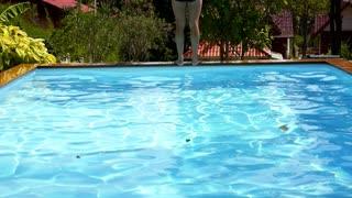 Man Falling and Splashing into Pool Water. Slow Motion.