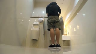 Man Peeing in Toilet with Urinals. 4K