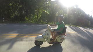 Man Riding a Vintage Scooter on Tropical Road