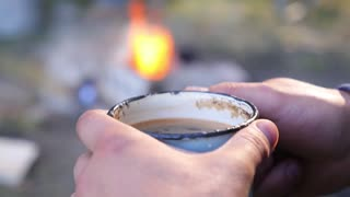 Man Traveler Hands Holding Cup of Coffee near Fire Outdoors at Camping