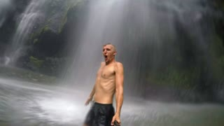 Man Under Great Waterfall on Bali Island in Tropical Jungles