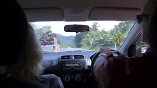 Middle Aged Couple Driving in Car on the Tropical Road