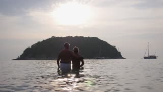 Middle-Aged Couple Embracing in Sea at Sunset