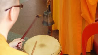 Monk in Orange Robe Playing Drum in Buddhist Monastery