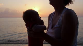 Mother and Baby in Sunset Time at the Sea. Slow Motion.