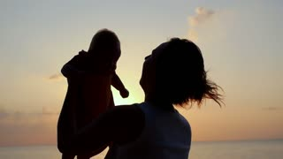 Mother with Little Baby at Sunset near the Sea. Slow Motion.