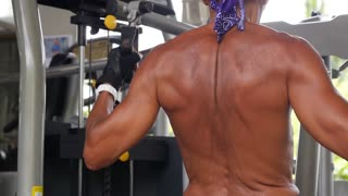 Muscular Body Building Man Training his Back at Gym