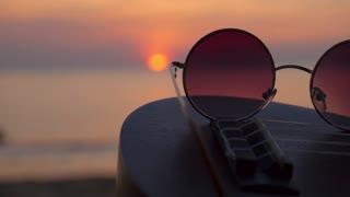 Ocean or Sea Sunset Through Hippie Sunglasses Lying on Ukulele