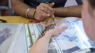 Painting Indian Henna or Mehendi Tattoo on Hand Closeup