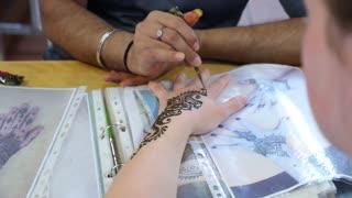 Painting Indian Henna or Mehendi Tattoo on Hand Closeup