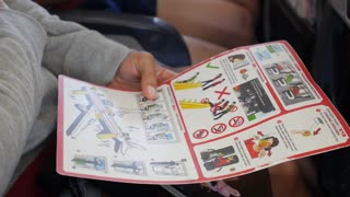 Passenger in Airplane Reading Safety Instructions on Board
