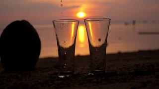 Pouring a Drink in Two Glasses on Beach in Sunset Light. Slow Motion.