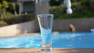 Pouring Fresh Water in a Glass near Swimming Pool. Slow Motion