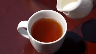 Pouring Milk from Porcelain Milk Jug into Cup with Tea. Slow Motion.