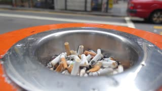 Public Ashtray Full of Cigarette Ends or Butt on City Street