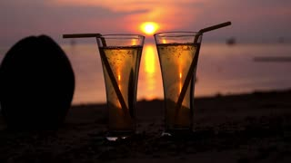 Romantic Beach Evening on Sunset with Two Glasses of Soft Drink
